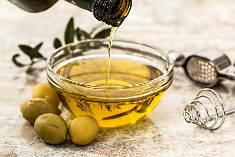 Olive oil being poured into a glass bowl