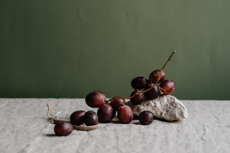Red grapes sitting on a gray marbled countertop, in front of a dark green background.