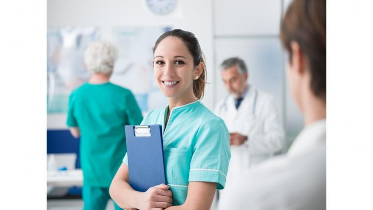 Young woman in medical scrubs holding a clipboard