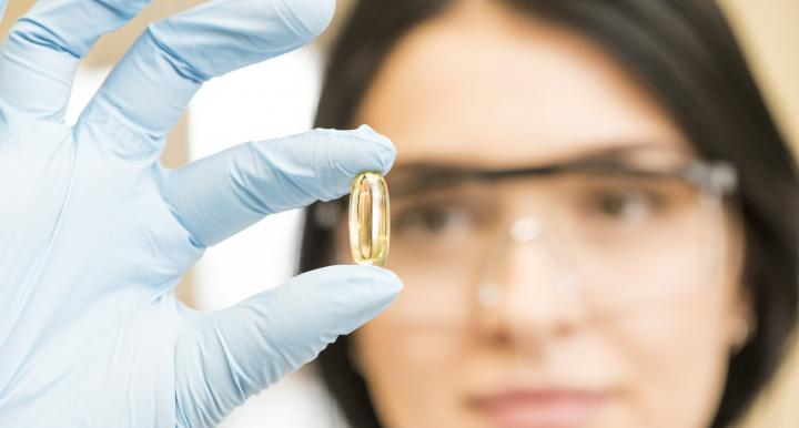 Female scientist examining omega-3 capsule.